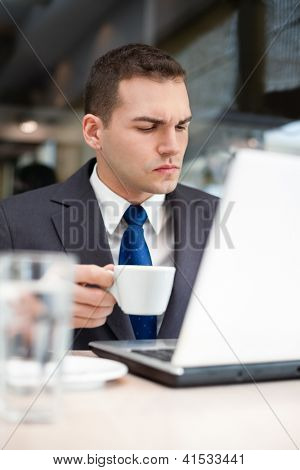 young man with a cup and a laptop in a cafe