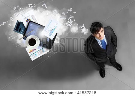 Image of business objects flying in air top view against businessman background