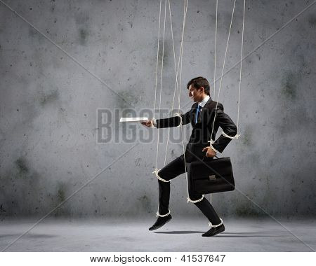 Image of businessman hanging on strings like marionette with briefcase in hand. Conceptual photography