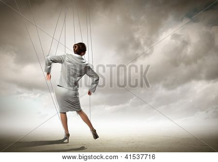 Image of businesswoman hanging on strings like marionette. Conceptual photography