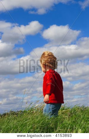 Young Boy Standing In A Field