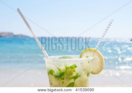 Cropped Mojito cocktail on the beach with blurred sea in the background