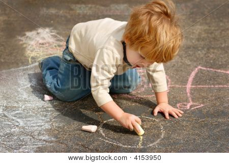 Boy Drawing Outside With Chalk