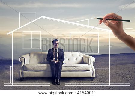 Businessman sitting on a white sofa in a wasteland, a hand drawing around him an home