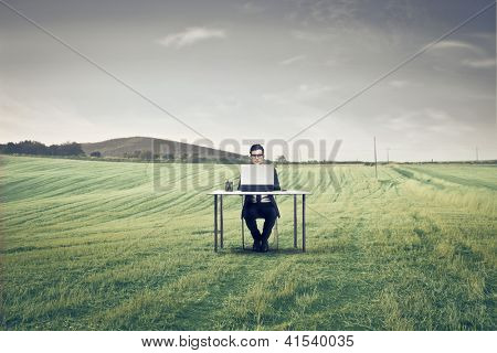 Businessman sitting at a desk on a large field using a laptop
