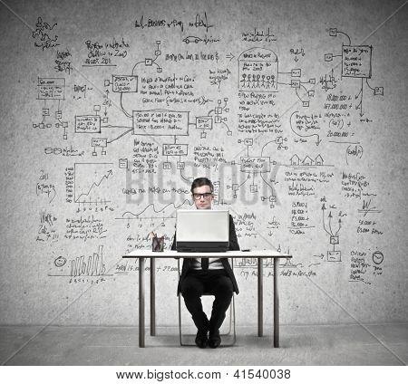 Geschäftsmann, arbeiten bei einem Laptop mit im Hintergrund eine Mauer voller Wirtschaft Zeichnungen