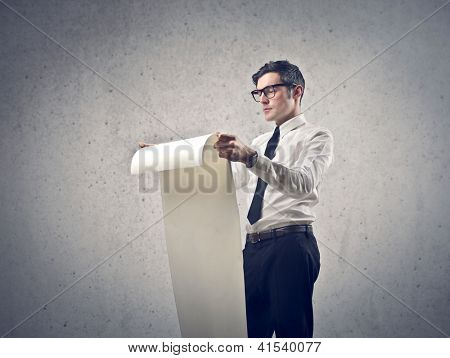 Office worker unrolling a long sheet