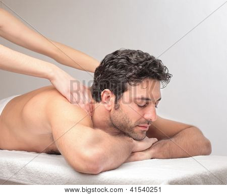 Man lying on a massage table is massaged by two female hands