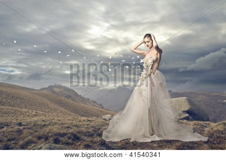 Elegant woman losing some petals in a wasteland