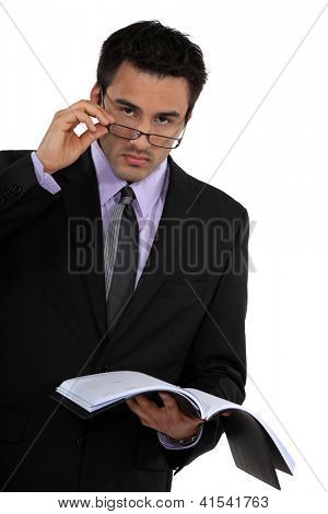 Businessman peering over his glasses and holding his agenda