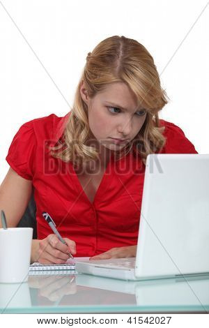 Woman writing notes from laptop