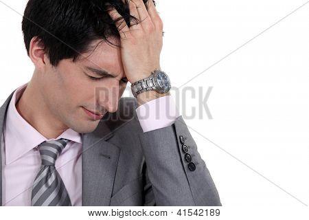 A portrait of a businessman having a headache.
