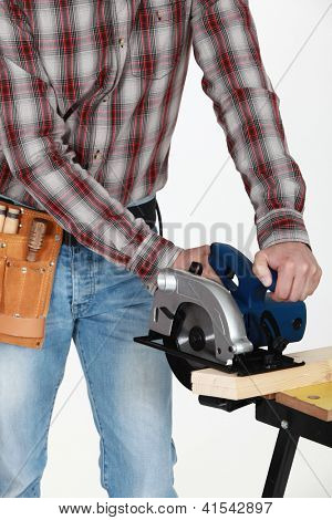 Craftsman with chainsaw cutting wood