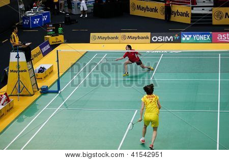 KUALA LUMPUR - JANUARY 15:Hong Kong's Cheung Ngan Yi (red) plays China's Xuan Deng at the Maybank Malaysia Open 2013 Badminton event qualifier played in Kuala Lumpur, Malaysia on January 15, 2013.