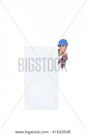 Female build stood by poster shushing