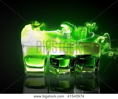 Three glasses of green absinth with fairy