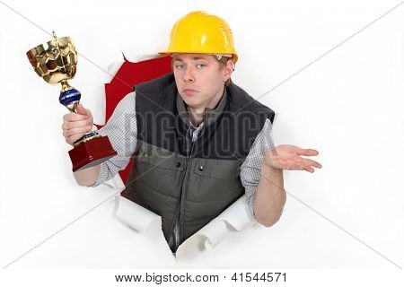 A construction worker holding a trophy cup.