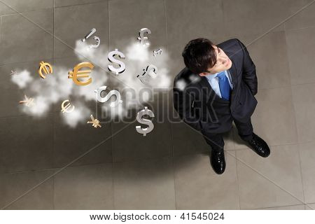 Top view of young businessman making decision currency signs in air