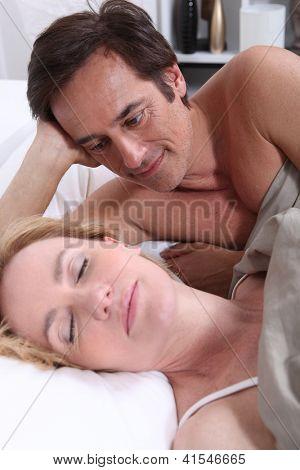 Man watching woman sleeping