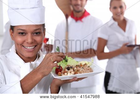 a cook holding a dish, a pizza cook and a waitress dressed in uniform