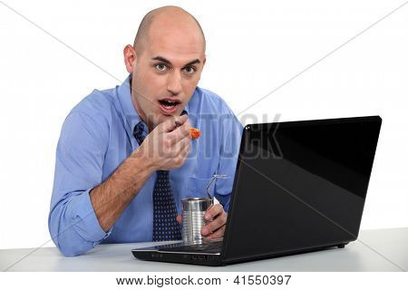 Man eating tinned food in front of his laptop