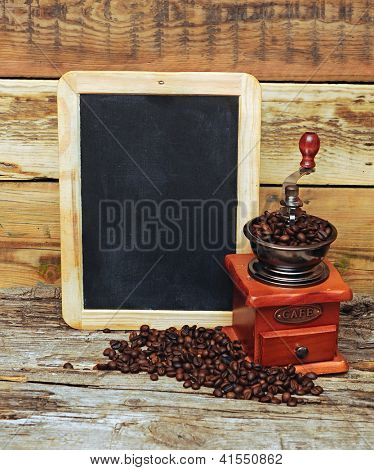 coffee mill and blank chalkboard over wooden background