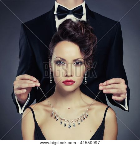 Elegant man on a beautiful woman wears a necklace