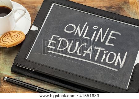 online education concept - white chalk handwriting on old slate blackboard displayed on a screen of digital tablet computer together with a cup of coffee