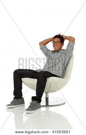 Young adult relaxing on a chair facing camera