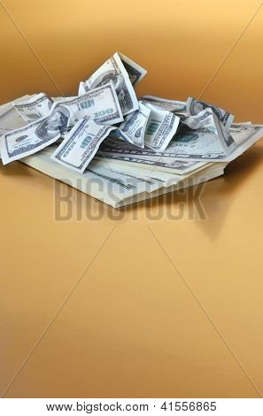 Stack of american dollar covered by small size one hundred dollar fake banknotes. Golden background.