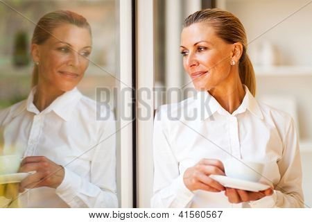 elegant senior businesswoman looking outside of office with coffee