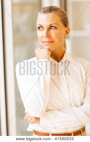 thoughtful female senior office worker looking outside window