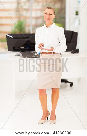 senior businesswoman drinking coffee in office