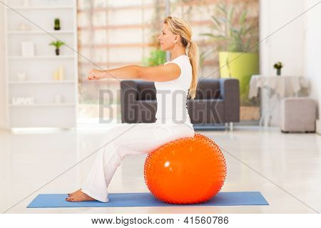 fit middle aged woman sitting on exercise ball at home
