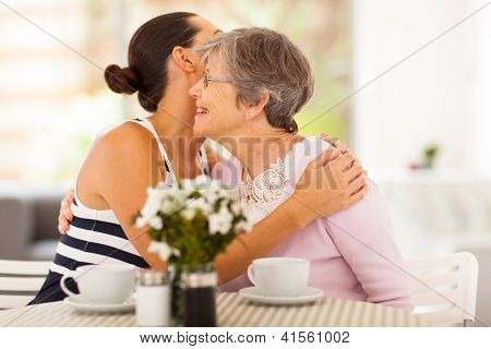 young woman hugging senior mother when visiting her