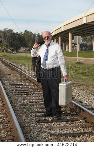 Jobless Senior Businessman Walking Along Railroad Train Track With Suitcase