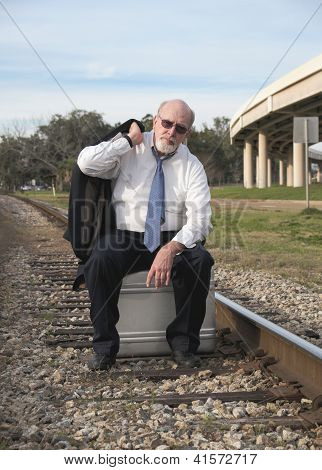 Jobless Senior Businessman Sits On Suitcase On Railroad Train Tracks