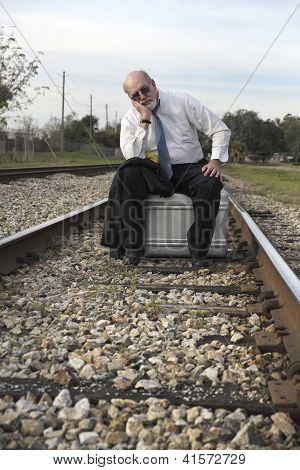 Unemployed Senior Businessman Sits On Suitcase On Railroad Train Tracks