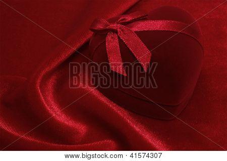Red Heart Shaped Gift Box On The Red Velvet