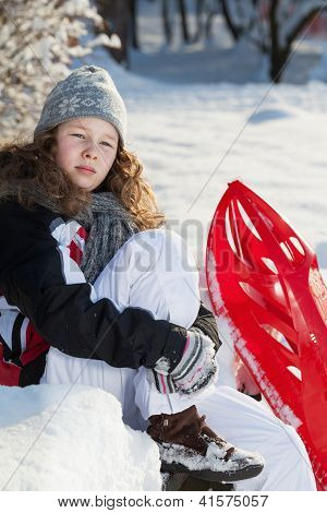 Girl With Red Plastic Sled In A Snowy Park