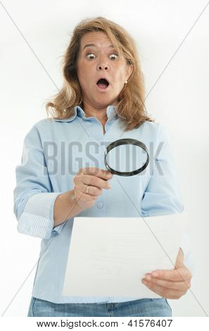 Woman with shocked expression examining a document thru a magnifying glass