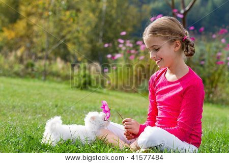 Happy childhood, puppy - lovely girl playing with cute puppy in the garden