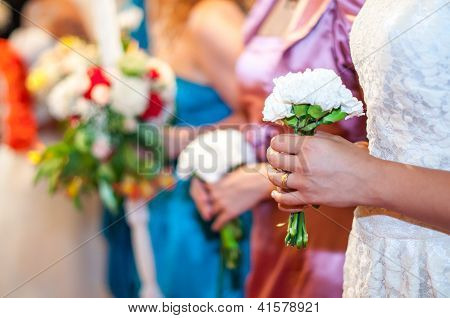 Bridesmaids holding flowers at wedding reception