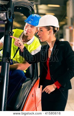 Forklift driver at warehouse of freight forwarding company, female super visor or coworker, pointing