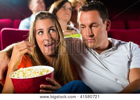 couple watching movie at movie theater and eating popcorn, he hugged her