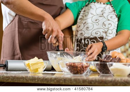 Asian couple, man and women, baking homemade cake in his kitchen for dessert
