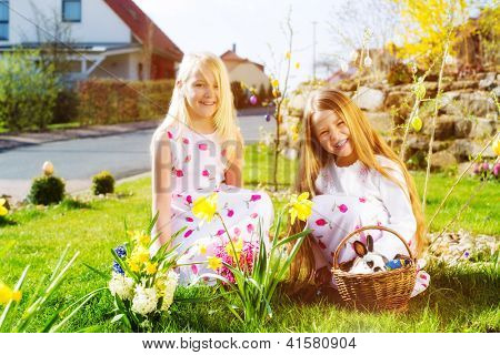 Children on an Easter Egg hunt on a meadow in spring, a living Easter Bunny is sitting in the Easter basket