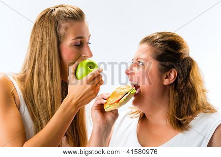 Healthy against unhealthy - Thin and fat woman eating an apple and sandwich