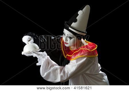 Curious Pierrot clown uncovering the lid of a dish