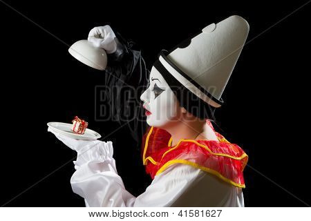 Mime Pierrot actor finding a gift under on a white dish tray
